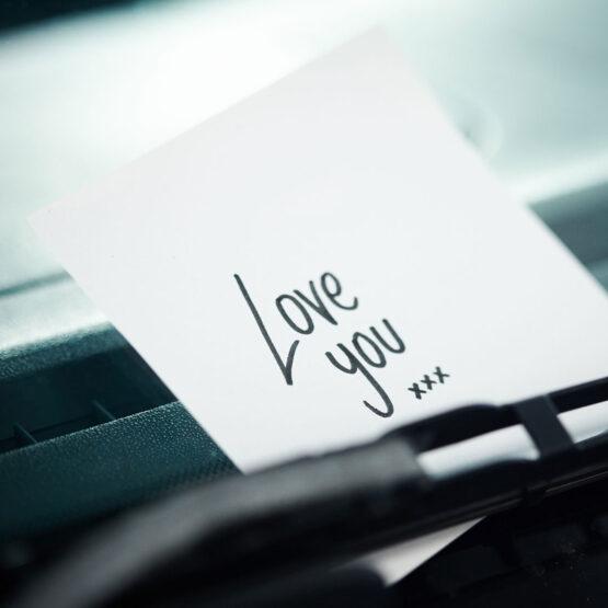 Handgeschriebene Liebesnotiz unter einem Scheibenwischer.